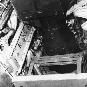Little Boy has been successfully lifted into the bomb bay and is being attached to sway brackets that will keep it secure