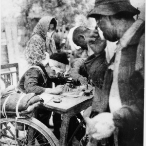 """Original Caption: """"An injured policeman writes relief certificates for rice rations to A-bomb survivors. Taken at tram stop near the Miyuki Bridge about 5pm, 2.4 kilometers from the hypocenter."""""""