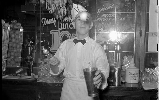 A soda jerker making a milkshake in the 1940s